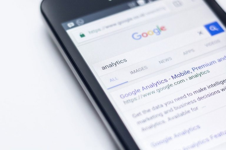 mobile phone with screen showing google analytics data of a landing page